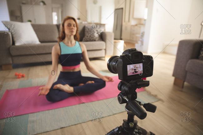 Caucasian woman spending time at home, in living room, exercising, practicing yoga and recording it with a camera. Social distancing during Covid 19 Coronavirus quarantine lockdown.