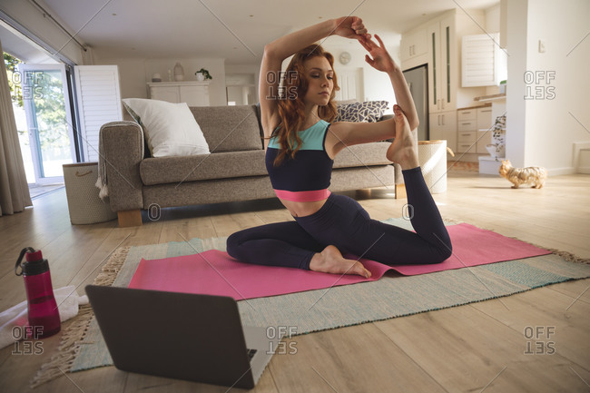 Caucasian woman spending time at home, in living room, exercising, practicing yoga while looking at laptop. Social distancing during Covid 19 Coronavirus quarantine lockdown.
