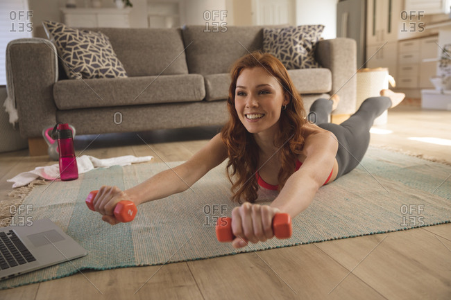 Caucasian woman spending time at home, in living room, exercising with dumbbells, using laptop. Social distancing during Covid 19 Coronavirus quarantine lockdown.