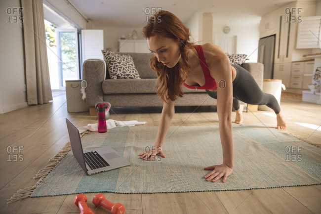 Caucasian woman spending time at home, in living room, exercising while looking at the laptop. Social distancing during Covid 19 Coronavirus quarantine lockdown.