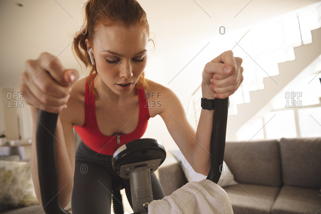 Caucasian woman spending time at home, in living room, exercising on stationary bike with her earphones in. Social distancing during Covid 19 Coronavirus quarantine lockdown.