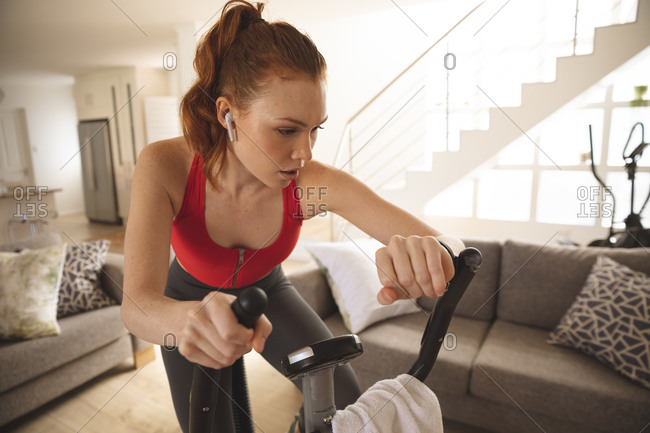 Caucasian woman spending time at home, in living room, exercising on stationary bike, checking her smartwatch. Social distancing during Covid 19 Coronavirus quarantine lockdown.
