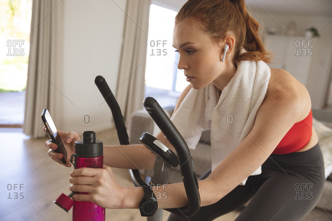 Caucasian woman spending time at home, in living room, exercising on stationary bike, using her smartphone. Social distancing during Covid 19 Coronavirus quarantine lockdown.