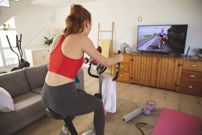 Caucasian woman spending time at home, in living room, exercising on stationary bike, watching tv. Social distancing during Covid 19 Coronavirus quarantine lockdown.