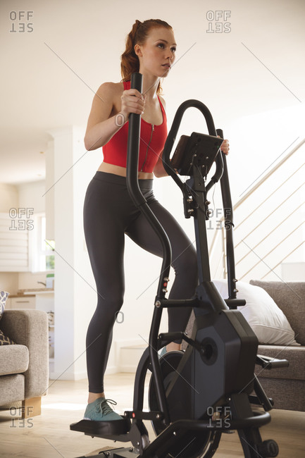 Caucasian woman spending time at home, in living room, exercising on cross trainer, wearing sportswear. Social distancing during Covid 19 Coronavirus quarantine lockdown.