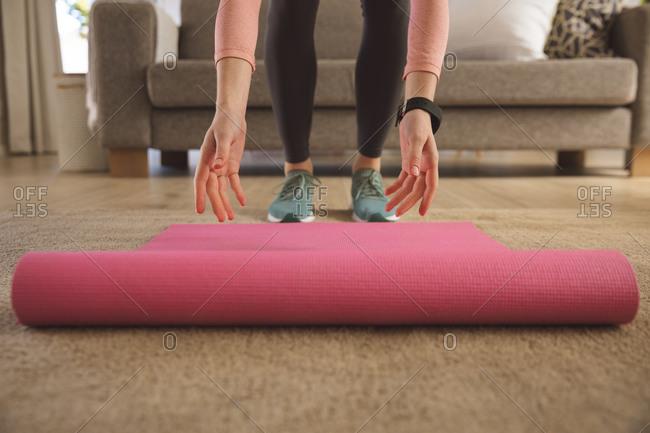 Caucasian woman spending time at home, in living room, unrolling yoga mat, preparing to exercise. Social distancing during Covid 19 Coronavirus quarantine lockdown.