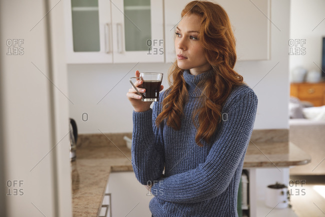 Caucasian woman spending time at home, in kitchen, looking serious, holding a cup, drinking coffee. Social distancing during Covid 19 Coronavirus quarantine lockdown.