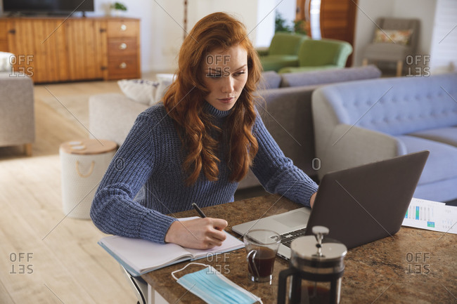 Caucasian woman spending time at home, in the kitchen, working from home, using her laptop and writing. Social distancing during Covid 19 Coronavirus quarantine lockdown.