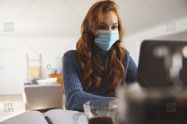 Caucasian woman spending time at home, in the kitchen, working from home, using her laptop,  wearing a face mask. Social distancing during Covid 19 Coronavirus quarantine lockdown.