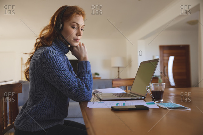 Caucasian woman spending time at home, in the kitchen, working from home, using her laptop,  wearing a headset. Social distancing during Covid 19 Coronavirus quarantine lockdown.