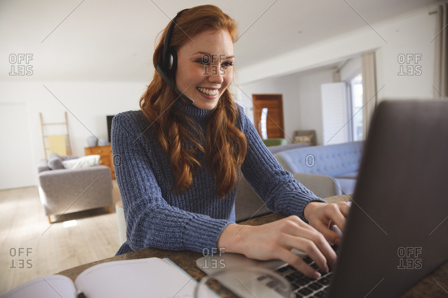 Caucasian woman spending time at home, in the kitchen, working from home, using her laptop, wearing a headset, smiling. Social distancing during Covid 19 Coronavirus quarantine lockdown.