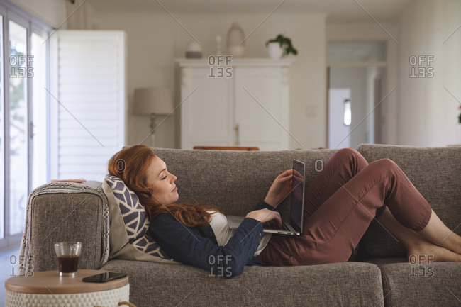 Caucasian woman spending time at home, in living room, using laptop, lying on the couch. Social distancing during Covid 19 Coronavirus quarantine lockdown.