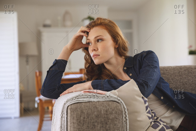 Caucasian woman spending time at home, in living room, lying on the couch, looking sad. Social distancing during Covid 19 Coronavirus quarantine lockdown.