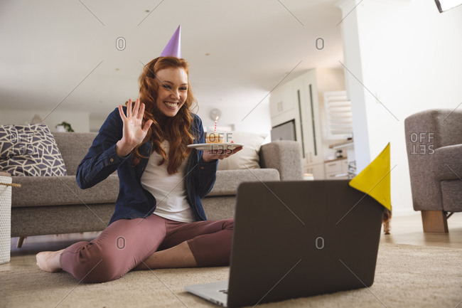 Caucasian woman spending time at home, in living room, smiling, celebrating, holding a cupcake with a candle. Social distancing during Covid 19 Coronavirus quarantine lockdown.