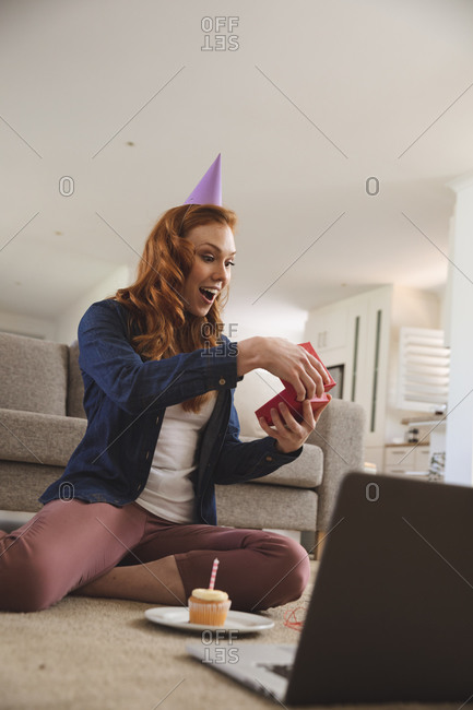 Caucasian woman spending time at home, in living room, smiling, celebrating, opening a gift, cupcake next to her. Social distancing during Covid 19 Coronavirus quarantine lockdown.