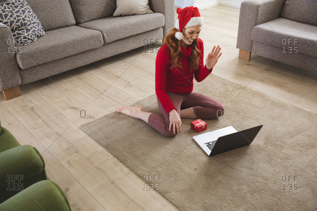Caucasian woman spending time at home, in living room, smiling, wearing Christmas hat, waving during a video call. Social distancing during Covid 19 Coronavirus quarantine lockdown.