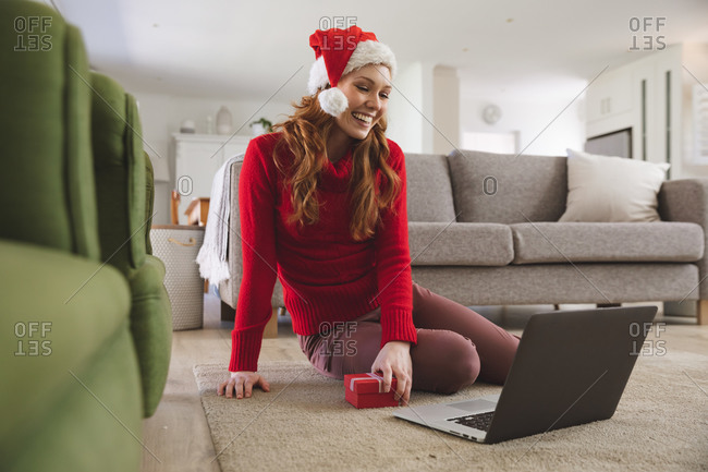 Caucasian woman spending time at home, in living room, smiling, wearing Christmas hat, holding a gift during a video call. Social distancing during Covid 19 Coronavirus quarantine lockdown.