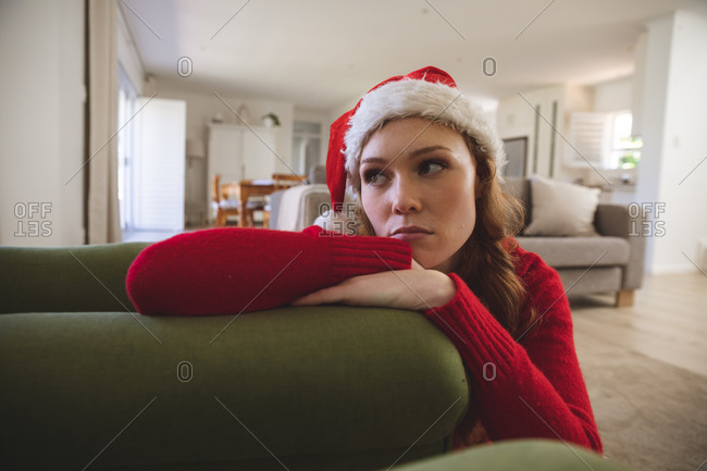 Caucasian woman spending time at home, in living room, looking sad, wearing Christmas hat and red jumper. Social distancing during Covid 19 Coronavirus quarantine lockdown.