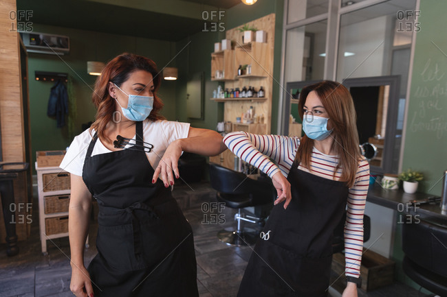 Two Caucasian female hairdressers working in hair salon wearing face masks, keeping distance and greeting by touching elbows. Health and hygiene in workplace during Coronavirus Covid 19 pandemic.