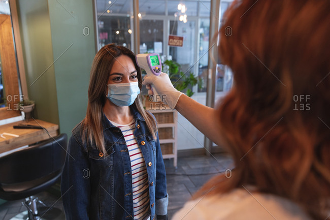 Caucasian female hairdresser working in hair salon, measuring temperature of a female Caucasian customer in face mask. Health and hygiene in workplace during Coronavirus Covid 19 pandemic.