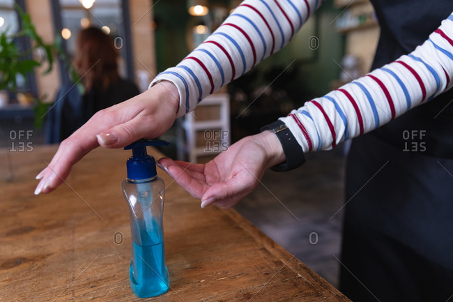 Mid section of Caucasian female hairdresser working in hair salon, applying hand sanitizer on her hands. Health and hygiene in workplace during Coronavirus Covid 19 pandemic.