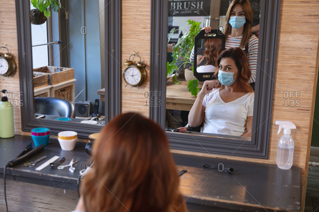 Caucasian female hairdresser working in hair salon wearing face mask, showing haircut to a female Caucasian customer in face mask. Health and hygiene in workplace during Coronavirus Covid 19 pandemic.