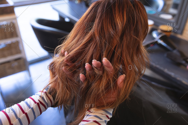 Caucasian female hairdresser working in hair salon, going through hair of female Caucasian customer with her fingers. Health and hygiene in workplace during Coronavirus Covid 19 pandemic.