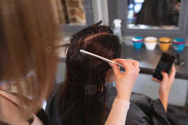 Caucasian female hairdresser working in hair salon, combing hair of female Caucasian customer using her smartphone. Health and hygiene in workplace during Coronavirus Covid 19 pandemic.