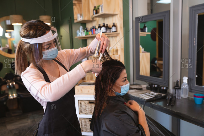 Caucasian female hairdresser working in hair salon wearing face mask, combing hair of female Caucasian customer in face mask. Health and hygiene in workplace during Coronavirus Covid 19 pandemic.