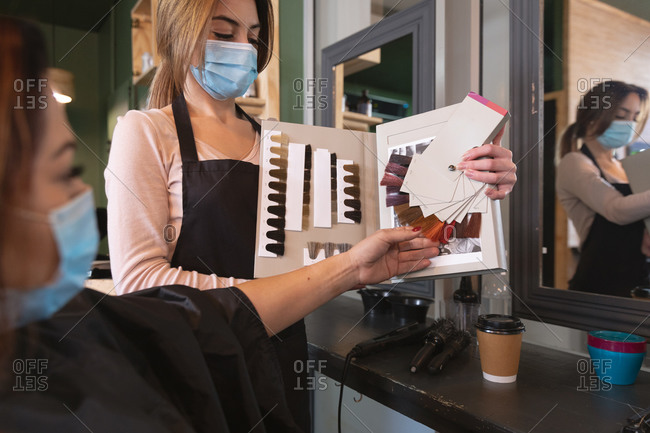 Caucasian female hairdresser working in hair salon wearing face mask, showing hair dyes to female Caucasian customer in face mask. Health and hygiene in workplace during Coronavirus Covid 19 pandemic.