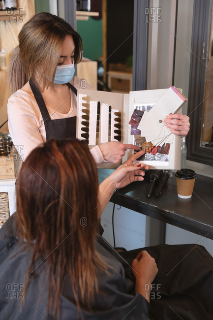 Caucasian female hairdresser working in hair salon wearing face mask, showing hair dyes to female Caucasian customer. Health and hygiene in workplace during Coronavirus Covid 19 pandemic.