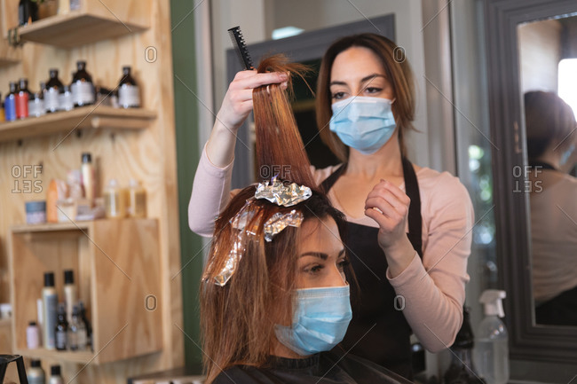 Caucasian female hairdresser working in hair salon wearing face mask, dying hair of female Caucasian customer in face mask. Health and hygiene in workplace during Coronavirus Covid 19 pandemic.