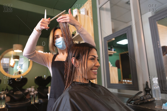 Caucasian female hairdresser working in hair salon wearing face mask, cutting hair of female Caucasian customer. Health and hygiene in workplace during Coronavirus Covid 19 pandemic.