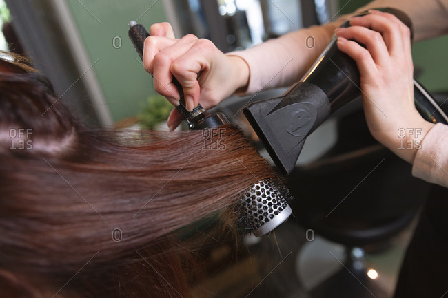 Hands of Caucasian female hairdresser working in hair salon, drying hair of female Caucasian customer. Health and hygiene in workplace during Coronavirus Covid 19 pandemic.