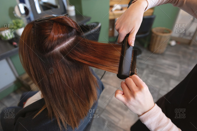 Hands of Caucasian female hairdresser working in hair salon wearing, straightening hair of female Caucasian customer. Health and hygiene in workplace during Coronavirus Covid 19 pandemic.