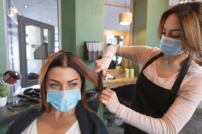 Caucasian female hairdresser working in hair salon wearing face mask straightening hair of female Caucasian customer in face mask. Health and hygiene in workplace during Coronavirus Covid 19 pandemic.