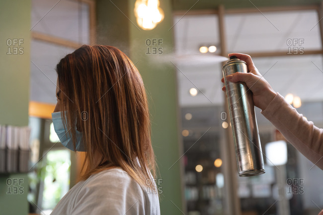 Caucasian female hairdresser working in hair salon spraying hairspray on hair of female Caucasian customer in face mask. Health and hygiene in workplace during Coronavirus Covid 19 pandemic.