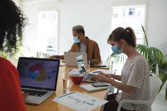 Multi ethnic group of male and female creative business colleagues working in modern office wearing face masks. Health and hygiene in the workplace during Coronavirus Covid 19 pandemic.
