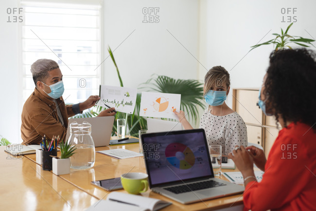 Multi ethnic group of male and female business creatives in meeting wearing face masks discussing documents. Health and hygiene in the workplace during Coronavirus Covid 19 pandemic.