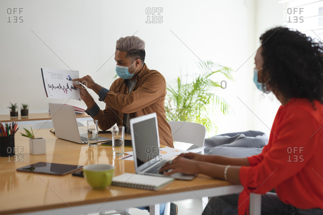 Mixed race male and female business creatives in meeting wearing face masks discussing documents. Health and hygiene in the workplace during Coronavirus Covid 19 pandemic.