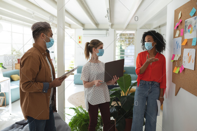 Multi ethnic group of male and female business creatives stand brainstorming in modern office wearing face masks. Health and hygiene in the workplace during Coronavirus Covid 19 pandemic.