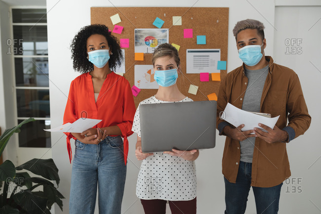 Portrait of multi ethnic group of male and female creative business colleagues wearing face masks in an office. Health and hygiene in the workplace during Coronavirus Covid 19 pandemic.