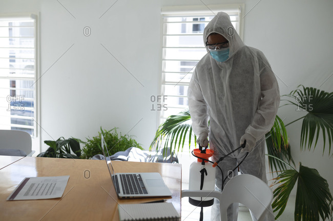 Mixed race male cleaner wearing anti-contamination overalls spraying disinfecting an office. Health and hygiene in the workplace during Coronavirus Covid 19 pandemic.