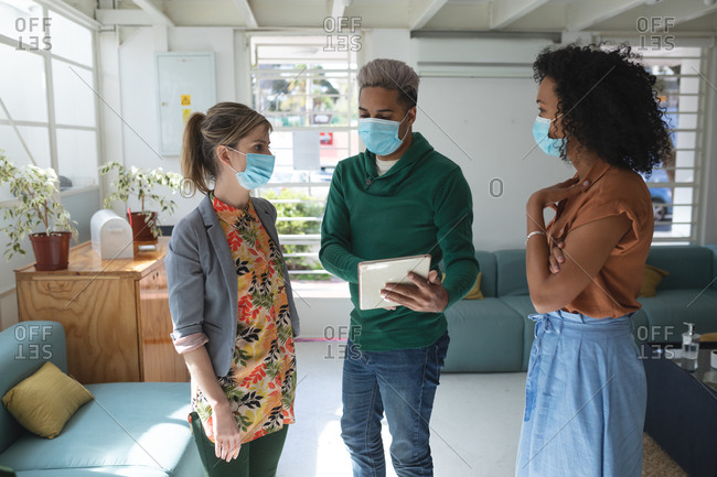 Multi ethnic group of male and female business creatives wearing face masks in office brainstorming using tablet. Health and hygiene in the workplace during Coronavirus Covid 19 pandemic.