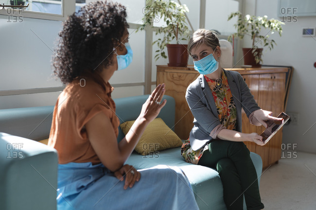 Mixed race and Caucasian female business creatives wearing face masks and distancing on sofa, talking and using tablet in office. Health and hygiene in workplace during Coronavirus Covid 19 pandemic.