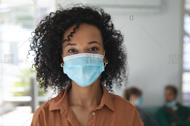 Portrait of mixed race female business creative standing in an office wearing face mask. Health and hygiene in workplace during Coronavirus Covid 19 pandemic.