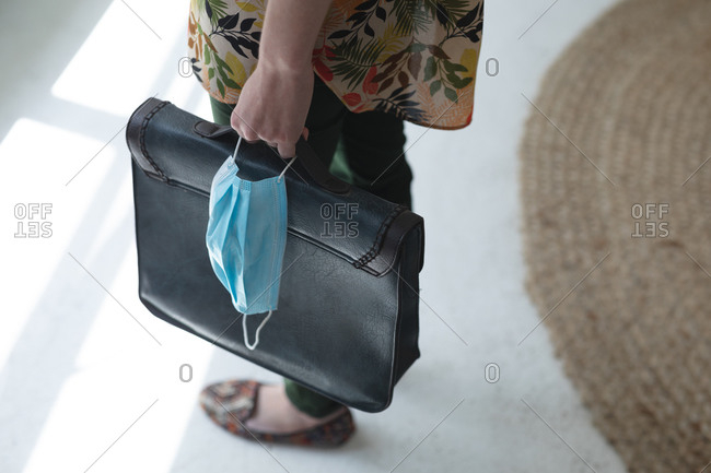 Mid section of female business creative standing in office foyer holding briefcase and face mask. Health and hygiene in workplace during Coronavirus Covid 19 pandemic.