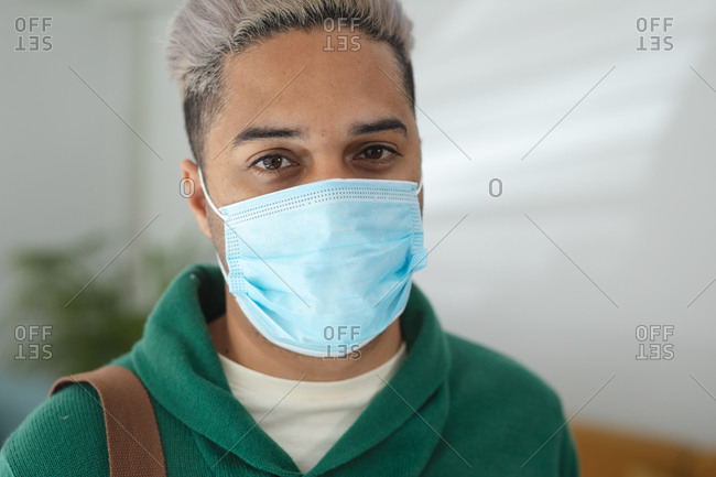 Portrait of mixed race male business creative standing in an office wearing face mask. Health and hygiene in workplace during Coronavirus Covid 19 pandemic.