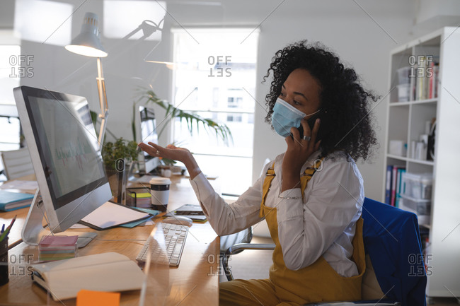 Mixed race woman working at desk in a modern office wearing a face mask and talking on a smartphone. Health and hygiene in the workplace during Coronavirus Covid 19 pandemic.