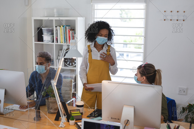 Mixed race and Caucasian female creative business colleague talking in office wearing face masks, male colleague in background. Health and hygiene in workplace during Coronavirus Covid 19 pandemic.